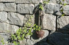 Старый cowbell на каменной стене стоковые изображения
