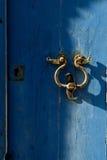 Старый knocker двери на сини Стоковые Изображения