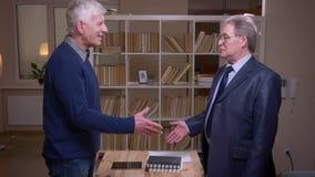 2 старых делового партнера трясут руки на предпосылке книжных полков подписывая контракт видеоматериал