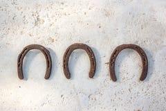 3 старых ржавых подковы вися на белой стене, символе везения Стоковые Фотографии RF