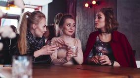 3 старых сексуальных друз имея trustful переговор в баре, держа стекла коктеилей спирта модный взгляд сток-видео