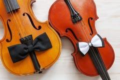 2 старых скрипки и 2 бабочки на белой деревянной предпосылке Взгляд сверху, конец-вверх стоковая фотография
