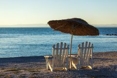2 старых шезлонги и зонтика солнца на предпосылке штиля на море Стоковое Изображение