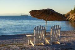2 старых шезлонги и зонтика солнца на предпосылке штиля на море Стоковое Изображение RF