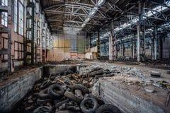 Старье автошин в покинутой промышленной зале Бывшая фабрика экскаватора Воронежа стоковые изображения