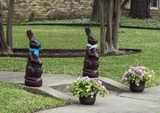 Статуи зайчика пасхи с баками цветков Стоковая Фотография RF