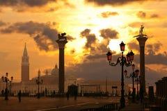 Статуи на столбцах, обслуживании гондолы на заходе солнца Стоковые Фото