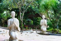 Статуи 2 сидя белых монахов Стоковые Изображения