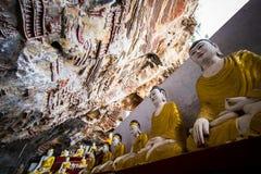 Статуи Buddhas и религиозный высекать в пещере чокнутого Kaw Hpa-An, стоковое фото rf