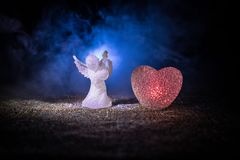 Статуэтка малых ангела и сердца и обручальных колец над синей туманной предпосылкой Стоковое Изображение
