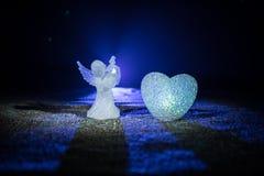 Статуэтка малых ангела и сердца и обручальных колец над синей туманной предпосылкой Стоковые Фото