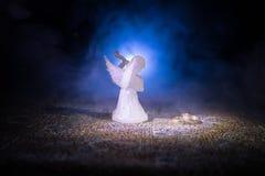 Статуэтка малых ангела и сердца и обручальных колец над синей туманной предпосылкой Стоковое фото RF