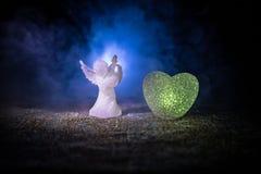 Статуэтка малых ангела и сердца и обручальных колец над синей туманной предпосылкой Стоковая Фотография RF