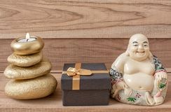 Статуэтка смеясь Будды с камнями и свечой, и подарочная коробка, на деревянной предпосылке, shui feng стоковые изображения rf