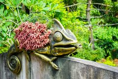 Статуя бронзы хамелеона с цветком на своей задней части украшенной внутри стоковая фотография rf