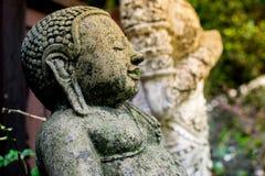 Статуя Будды сделала камня с мхом стоковая фотография rf