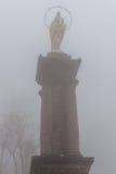 Статуя девой марии в предпосылке неба тумана Стоковое Фото