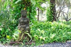 Статуя девушки, статуя смотрит на усмехаясь молодую женщину, одетую в tr Стоковые Изображения RF