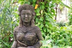 Статуя девушки, статуя смотрит на усмехаясь молодую женщину, одетую в tr Стоковая Фотография