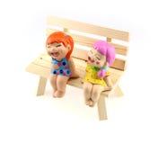 Статуя 2 детей к счастливому и улыбке, сидя на деревянном c Стоковые Изображения