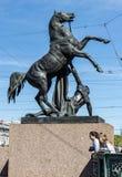 Статуя лошади более Tamer на мосте Anichkov и 2 маленьких девочках на ноге статуи Стоковое Изображение RF