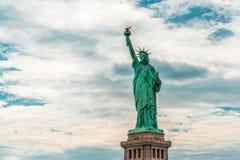 Статуя свободы Нью-Йорка против пасмурной предпосылки голубого неба, космоса экземпляра стоковые фото