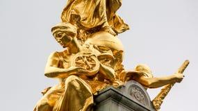 Статуя сидя колеса золота женского держа Стоковые Фотографии RF