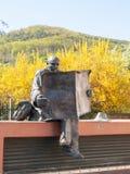 Статуя человека читая газету Стоковая Фотография