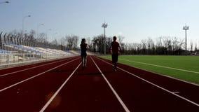 Стадион подходящих активных молодых привлекательных пар мальчика девушки бежать jogging внешний большой разрабатывая outdoors тре сток-видео