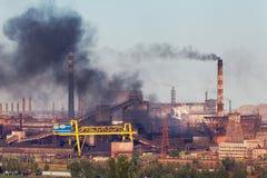 Стальная фабрика с смогом на заходе солнца Трубы с черным дымом Стоковое Изображение