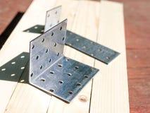сталь 90 deegrees пефорировала крепежную деталь угла на столе Стоковое Фото