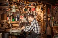 Стежки мужского работника шить на поясе в кожаной мастерской Стоковое Изображение RF