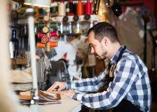 Стежки мужского работника шить на поясе в кожаной мастерской Стоковая Фотография