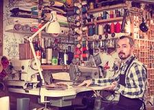 Стежки мужского работника шить на поясе в кожаной мастерской Стоковая Фотография RF