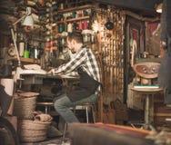 Стежки мужского работника шить на поясе в кожаной мастерской Стоковые Изображения RF