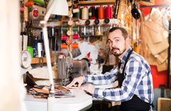 Стежки мужского работника шить на поясе в кожаной мастерской Стоковые Фотографии RF
