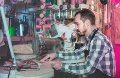 Стежки мужского работника шить на поясе в кожаной мастерской Стоковые Фото