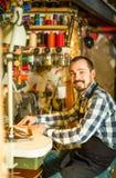 Стежки мужского работника шить на поясе в кожаной мастерской Стоковое Фото