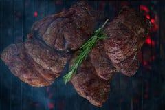 2 стейка говядины на гриле решетки с дымом стоковое фото rf