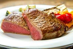 Стейки говядины на белом блюде с зажаренными овощами Стоковая Фотография