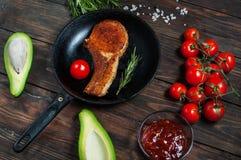Стейк в томатах сковороды, авокадоа и вишни на таблице Стоковые Изображения RF
