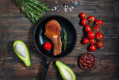 Стейк в томатах сковороды, авокадоа и вишни на таблице Стоковая Фотография RF