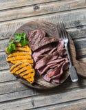 Стейк говядины и зажаренная тыква на разделочной доске на деревянной предпосылке Стоковые Фото