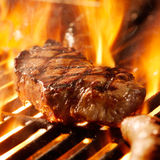 Стейк говядины на решетке с пламенами. Стоковая Фотография