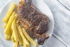 Стейк говядины с зажаренными картошками на плите Стоковые Фото