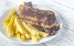 Стейк говядины с зажаренными картошками на плите Стоковая Фотография