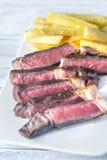 Стейк говядины с зажаренными картошками на плите Стоковая Фотография RF