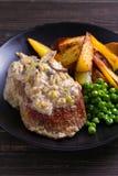 Стейк говядины diane с соусом гриба и лук-порея cream, фраями картошки и зелеными горохами стоковая фотография