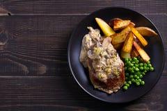 Стейк говядины diane с соусом гриба и лук-порея cream, фраями картошки и зелеными горохами стоковая фотография rf