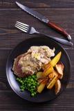 Стейк говядины diane с соусом гриба и лук-порея cream, фраями картошки и зелеными горохами стоковое фото rf